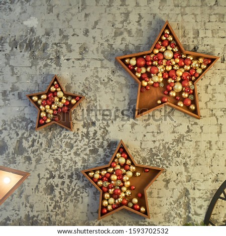 New Year's decoration, decoration of the wall.Wooden stars with balls of gold and red color.