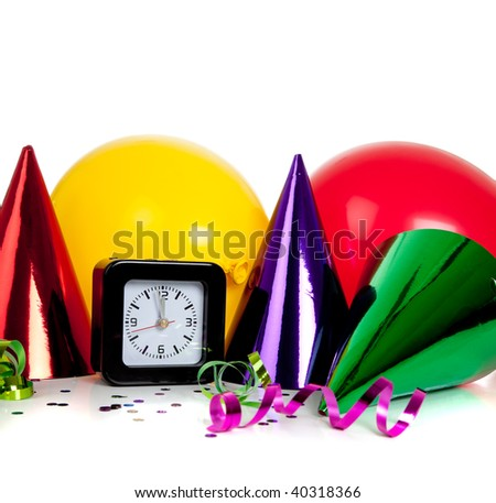 New Year's eve decorations including black clock set to midnight and party hats, streamers, confetti and balloons - stock photo