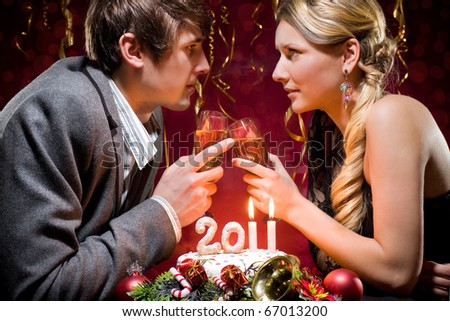 New Year's Eve of two beautiful young people with a cake with candles and other Christmas decorations