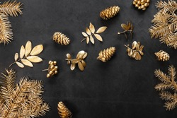 New Year's flat lay in golden and black shades. Spruce branches, leaves, cones and berries are painted with golden paint. Stylish concept of christmas, celebration. Top view, minimalism, copy space.