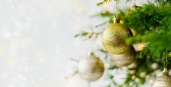 New Year's gold shiny ball hanging on a fir branch. Lights and garlands on a gray snow background. Christmas and happy new year concept, space for text for your design. Wallpaper.