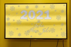 New Year's greetings in Brazil and Portugal in trending colors of 2021 means Happy New Year. Text on a modern TV screen hanging on the wall.