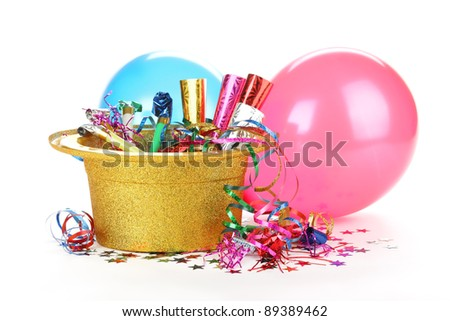 New Year's hat filled with noise makers, streamers and balloons on white background.