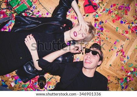 New Year\'s Party. Girl and boy laying on the floor full of confetti