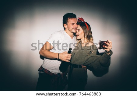 New Year's Party. Girl and boy posing in front of white wall and taking selfie