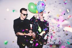 New Year's Party. Girl and boy posing in front of white wall with balloons