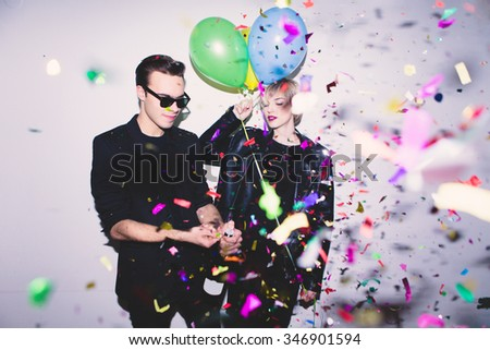New Year\'s Party. Girl and boy posing in front of white wall with balloons