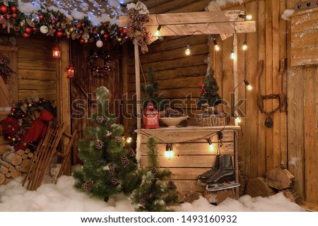 New Year's photo zone with snow near a wooden house. Christmas decor: toys, Christmas trees, skis, garland, firewood, glowing light bulbs. festive mood. picture for postcard
