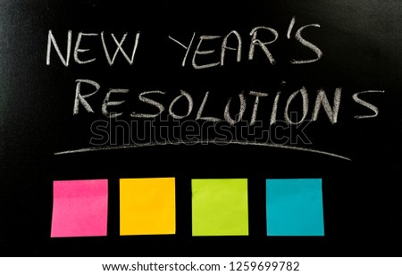 New Year's resolution written on blackboard with colorful blank notes copy space for dreams wishes and trendy lettering for happy life goals and self management concept and brick wall background. #1259699782