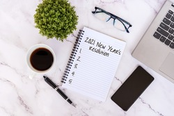 New Year's Resolutions 2021 text on note pad with smart phone, laptop, coffee, eyeglasses and pen.