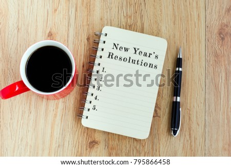 New Year's Resolutions text on notepad with pen and a cup of coffee, wooden background  - Shutterstock ID 795866458