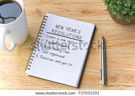 New year's resolutions written on notepad with pen, cup of coffee and flower on top of wooden table.  #737035591
