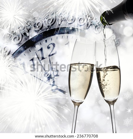 New Year\'s - toasting with champagne glasses against fireworks and clock close to midnight