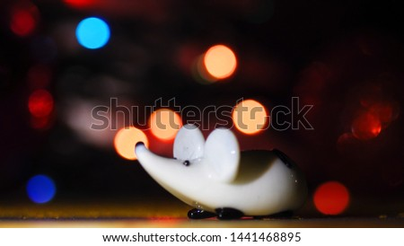 New Year's white rat. Christmas rat on the background of blurry lights and shooting fireworks. Christmas Rat