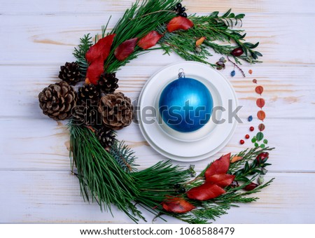 New Year's wreath of twig of twigs and flowers with white dishes on the table #1068588479