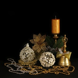 New year themed card with shine white baubles, sparkling pine cones, brass bell and unlighted candle in brass candelabra, jewellery on dark background.