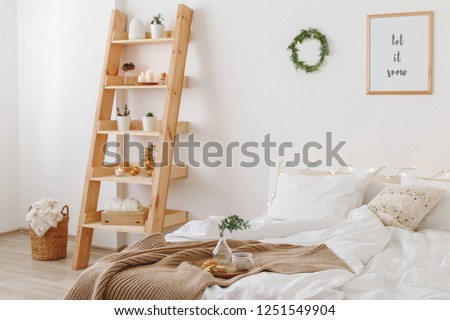 New year winter home interior decor. Christmas holiday decorated room. Stylish cozy bedroom: bed, wooden shelving, wicker basket, knitted blanket, plaid, wreath of pine branches, led garland lights. #1251549904