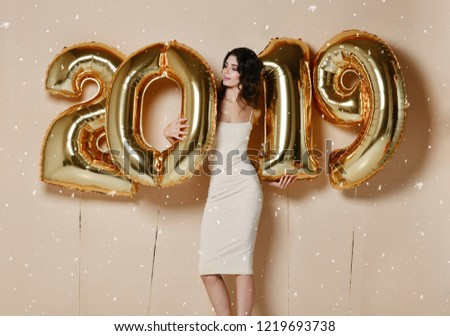 New Year. Woman With Balloons Celebrating At Party. Portrait Of Beautiful Smiling Girl In Shiny Golden Dress Throwing Confetti, Having Fun With Gold 2019 Balloons On Background. High Resolution.