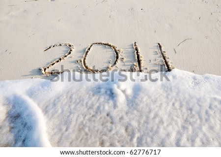 New year 2011 written in the sand while a wave coming in. Cuba
