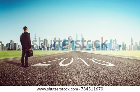New year 2018 ,young businessman looking on city skyline background . Determined to start concept . #734511670
