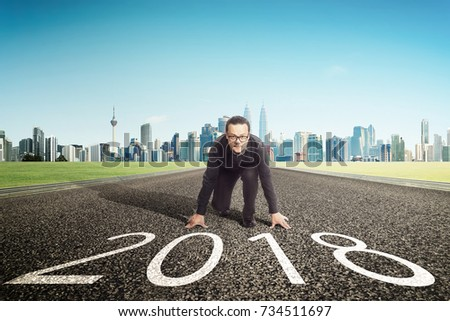 New year 2018 ,young businessman starting position to his career with city skyline background . Determined to start concept . #734511697