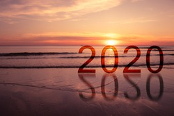 New Years Concept : 2020 words on seashore with beautiful seascape view in twilight time with sunset in background.