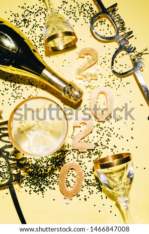 New Years Eve celebration background with champagn glass, 2020 number made with golden glitter candles, christmas decoration around, flatlay over a golden board, luxury  holiday concept