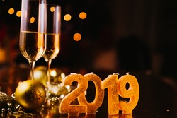 New Years Eve celebration background with pair of flute,candles forming the 2019 number, glitter and defocused background, with christmas tree light forming a nice bokeh, holiday concept.