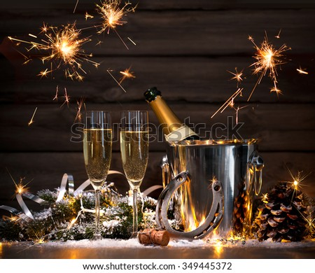 New Years Eve celebration background with pair of flutes and bottle of champagne in bucket and a horseshoe as lucky charm #349445372