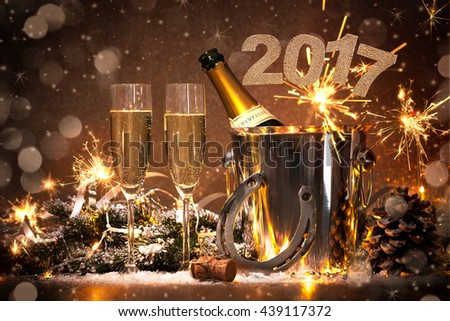 New Years Eve celebration background with pair of flutes and bottle of champagne in  bucket  and a horseshoe as lucky charm #439117372