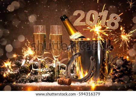 New Years Eve celebration background with pair of flutes and bottle of champagne in  bucket  and a horseshoe as lucky charm