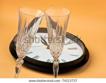 New years eve- clock showing 1 minute past midnight with champagne glasses