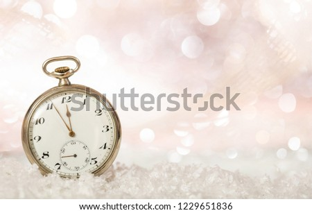 New Years eve countdown. Minutes to midnight on an old fashioned pocket watch, bokeh snowy background, copy space #1229651836