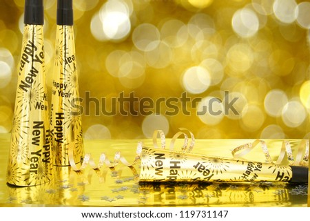 New Years Eve noisemakers and confetti with twinkling gold light background