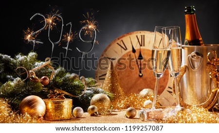 New Years Eve 2019 party background with flutes of champagne, decorations, and a clock counting down to midnight #1199257087