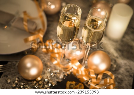 new years eve party table with champagne flute ribbon and golden glitter