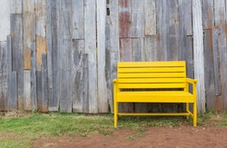 New yellow chair with old wood wall on grass.