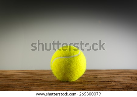 New yellow tennis balls on a wooden table. In light and shadow. Copy space room text.