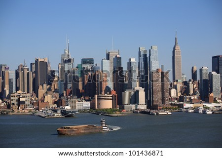 NEW YORK - APRIL 29: The Manhattan skyline with tugboat and barge on the Hudson River on April 29, 2012 in NY. First settled in 1624, New York City now has a population of over 8 million people. - stock photo
