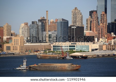 NEW YORK - APRIL 29: The Manhattan skyline with tugboat and barge on the Hudson River on April 29, 2012 in New York. First settled in 1624, New York City now has a population of over 8 million people.