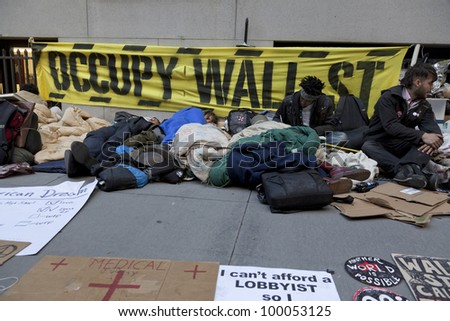 NEW YORK - APRIL 13: Unidentified demonstrators with 'Occupy Wall Street' on the sidewalk of Broad street and Wall street in Manhattan on April 13, 2012 in New York.