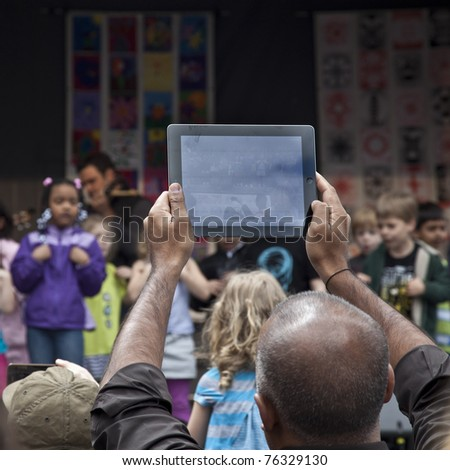 NEW YORK - APRIL 30: Unidentified guest records with iPad 2 performance of kids on stage at Family Festival on Greenwich street as part of 2011 Tribeca Film Festival on April 30, 2011 in New York City