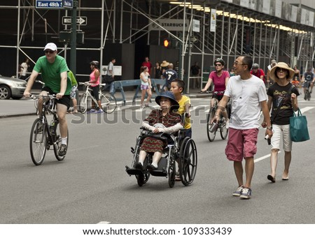 NEW YORK - AUGUST 04: Unidentified family with disabled senior walks along Park Avenue during Summer Streets sponsored by Department of Transportation in Manhattan on August 4, 2012 in New York