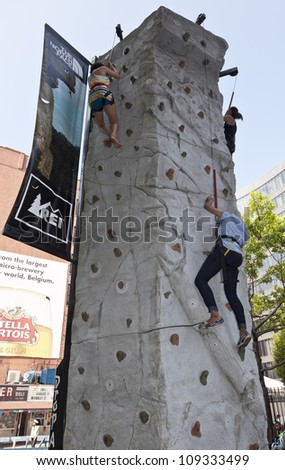 people climbing wall sponsored by REI store & The North Face clothing