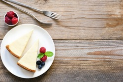 New York cheesecake or classic cheesecake with fresh berries on white plate, wooden table background and copy space for text
