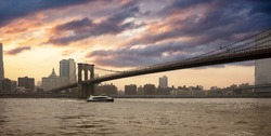 New York City and the Brooklyn Bridge along the East River, cloudy sky at sunset background. United states of America