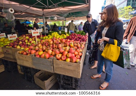 NEW YORK CITY - APR. 20: Woman selects produce at Union Square Greenmarket in NYC on Apr 20, 2012. This world famous farmers' market began in 1976 and has grown to 140 farmers during peak season. - stock photo