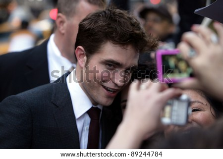 "NEW YORK CITY - APRIL 17: Actor Robert Pattinson greets a crowd of fans at the worldwide premiere of 20th Century Fox's ""Water For Elephants"" in New York City on April 17, 2011."