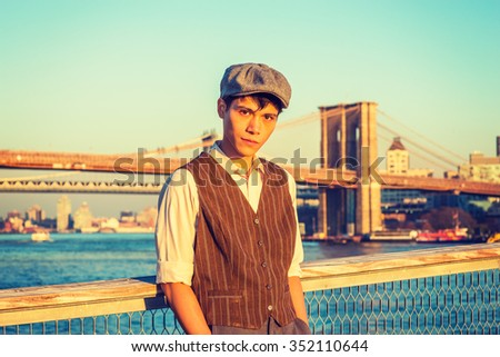 New York City Boy. Wearing newsboy cap, light yellow shirt, patterned vest, Asian American college student standing at harbor in sunset. Manhattan, Brooklyn bridges on background. Instagram effect.
