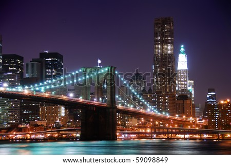 New York City Brooklyn Bridge and Manhattan skyline with skyscrapers over Hudson River illuminated with lights at dusk after sunset.